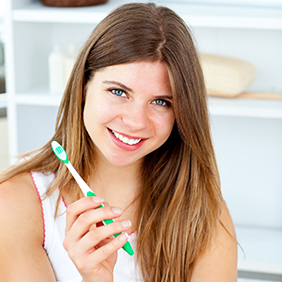Delighted woman holding a toothbrush smiling at the camera in the bathroom